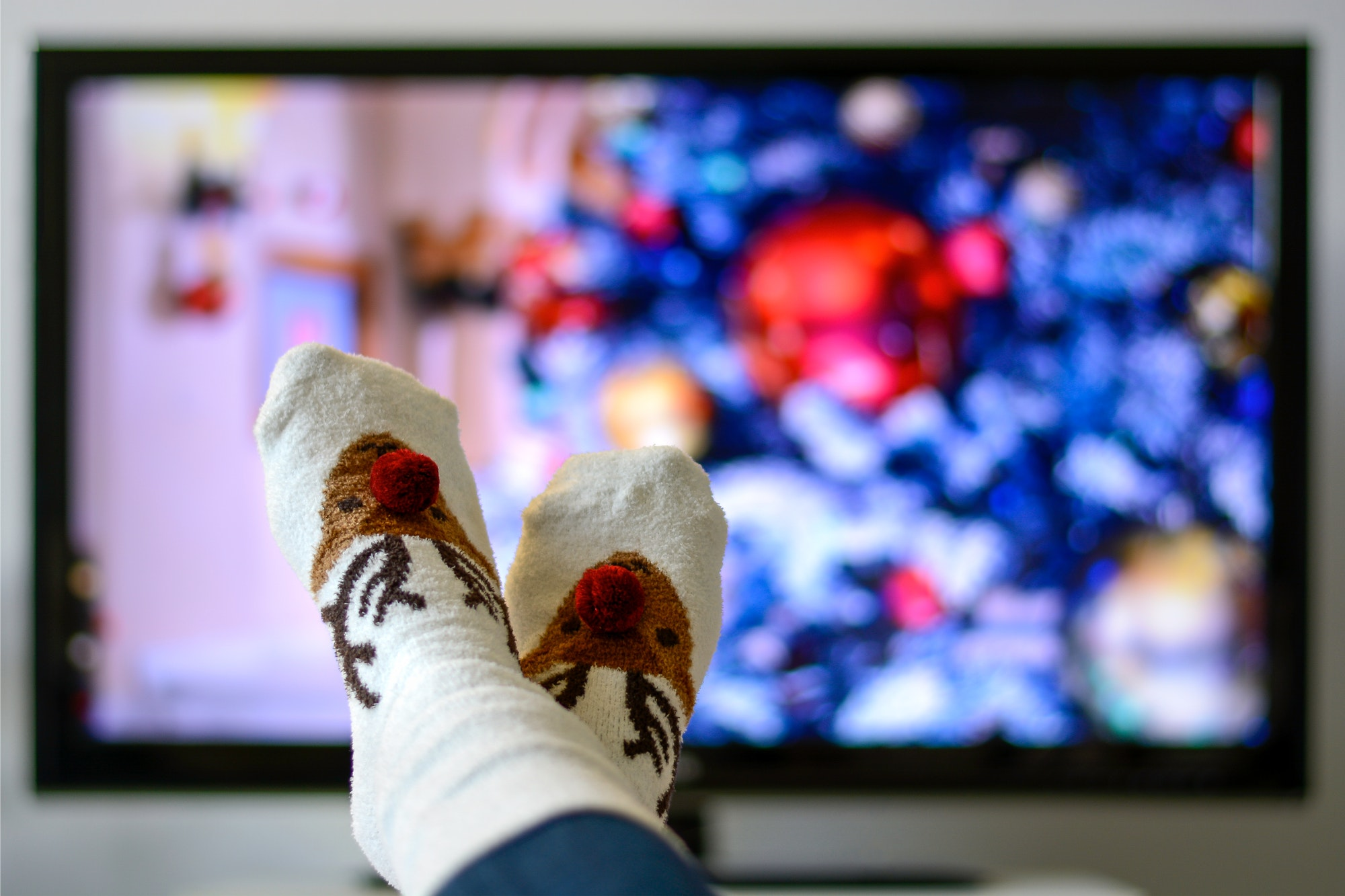 Christmas socks with reindeer and television with christmas tree in background