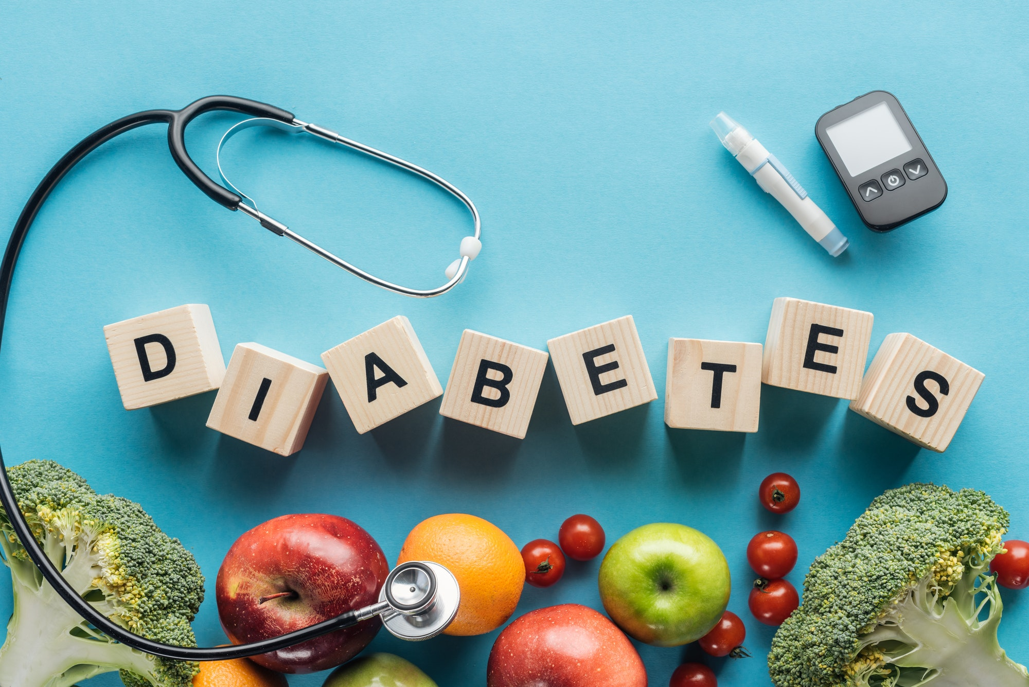 diabetes lettering made of wooden cubes with medical equipment and fruits on blue background