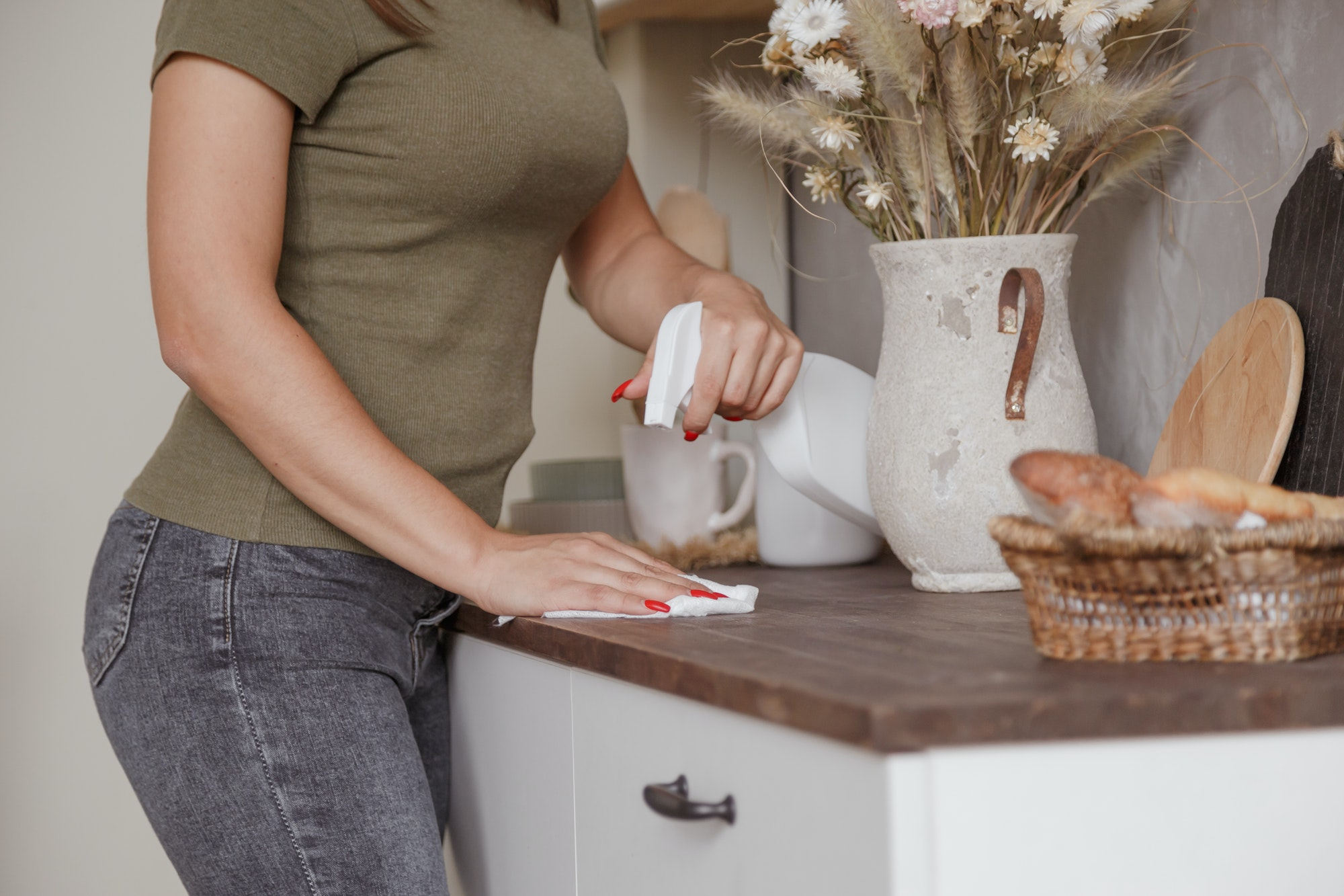 Young woman without gloves cleaning table with spray rag in kitchen